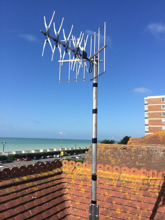 Traditional style TV aerial on a metal extension pole on top of a roof overlooking the beach.