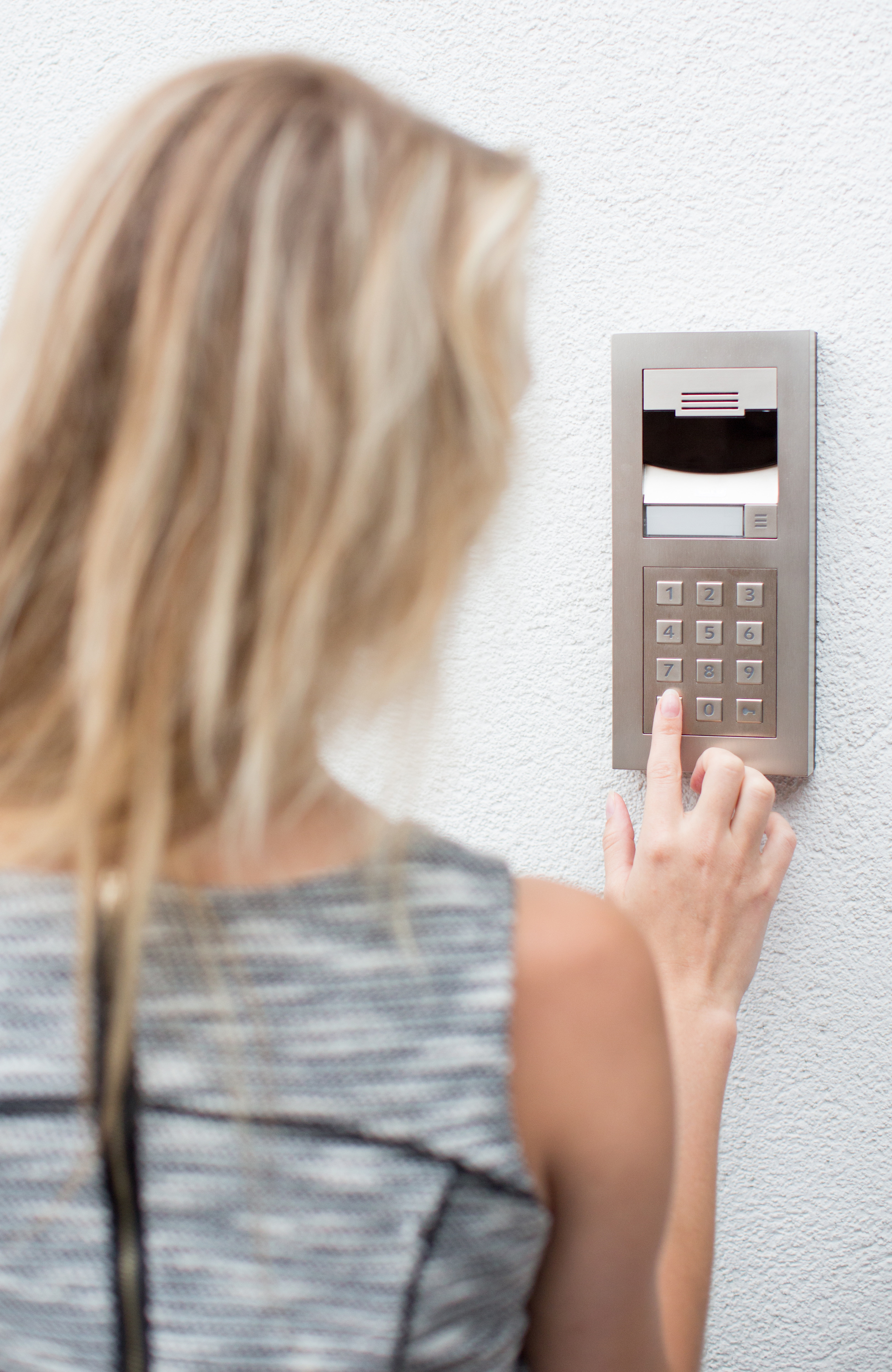 Woman using a button access control panel on a white wall