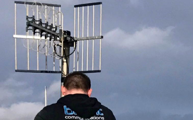 Briant Communications staff member working on an aerial against a blue sky
