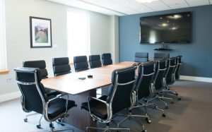 Meeting room and table with chairs facing a large television and webcam