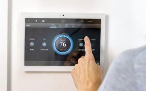 Touch sensitive digital heating control panel mounted on a light coloured wall.