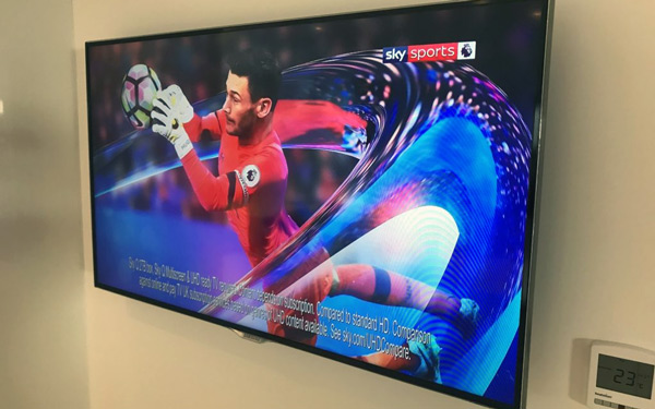 Flatscreen television hanging on a light coloured wall showing SKY sports.